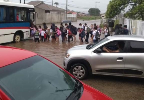 Estudantes enfrentam rua alagada para voltar para a casa no Jaqueline
